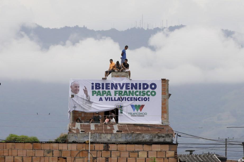 Des résidents sont assis sur le toit d'une maison afin d'avoir une meilleure vue sur la messe du pape François, à Villavicencio, en Colombie. | 8 septembre 2017