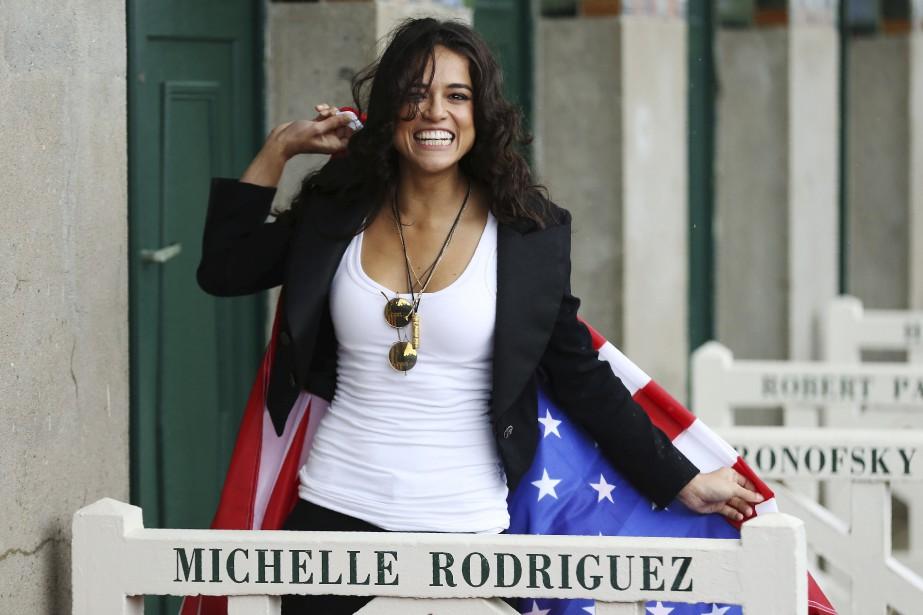 L'actrice américaine Michelle Rodriguez pose avec le drapeau des États-Unis lors de la 43 e  édition du Festival du film américain de Deauville, en France.  | 8 septembre 2017