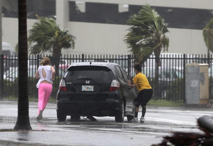 Des gens sont gênés par les vents d'<em>Irma</em> alors qu'ils tentent de gagner leur voiture, dans l'archipel des Keys. (AP)