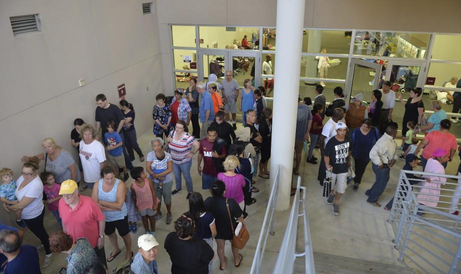 Des gens faisaient la file pour recevoir un petit déjeuner dans une école secondaire de Sarasota convertie en centre de crise temporaire. (AP)