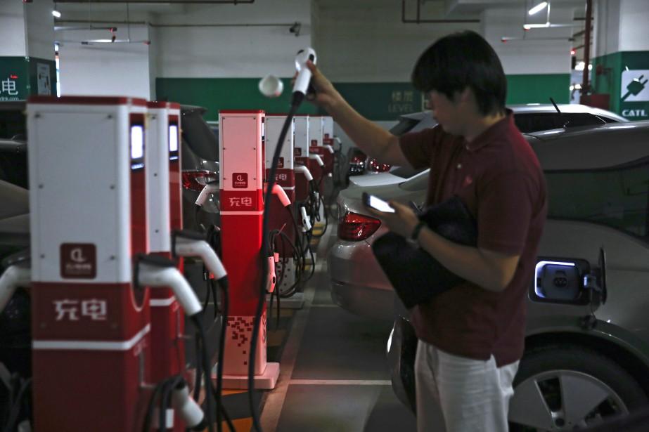 Un automobiliste s'apprête à brancher sa voiture électrique... (photo : AP)