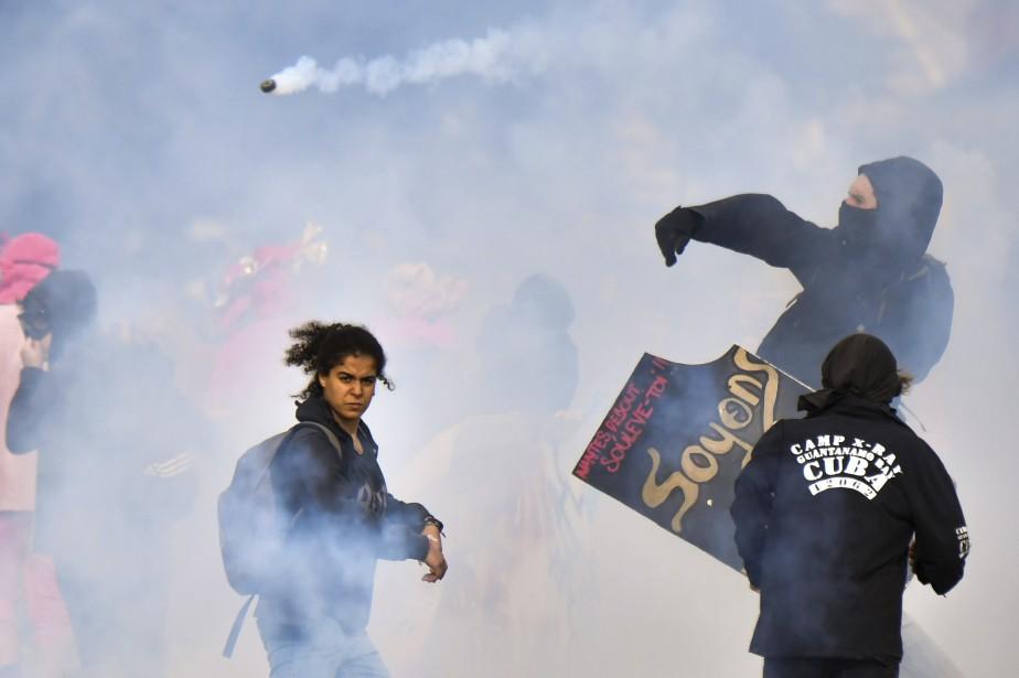 Un manifestant relance une grenade lacrymogène vers les policiers anti-émeute lors d'un rassemblement contre la réforme des travailleurs en France. Une grève générale et plus de 180 manifestations ont été organisées à travers le pays. | 12 septembre 2017