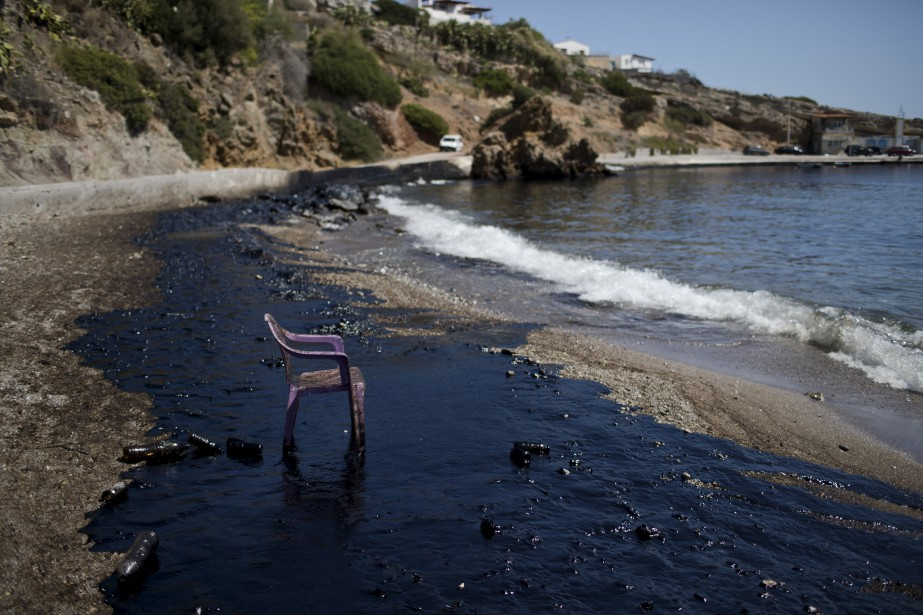 Une chaise de plastique est posée sur une plage en Grèce, alors que la marée noire se répand suite au naufrage d'un pétrolier, qui a déversé 2 200 tonnes de pétrole dans la mer Méditerranée. | 12 septembre 2017