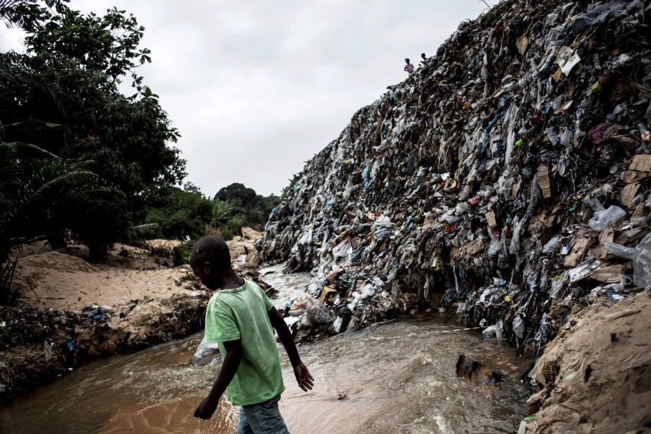 Un garçon marche à travers une rivière souillée de déchets dans un quartier de Kinshasa, en République Démocratique du Congo. | 12 septembre 2017