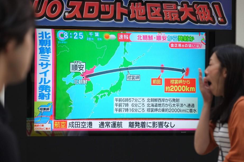 Des passants regardent la télévision à Tokyo diffusant... (PHOTO Kazuhiro NOGI, AFP)