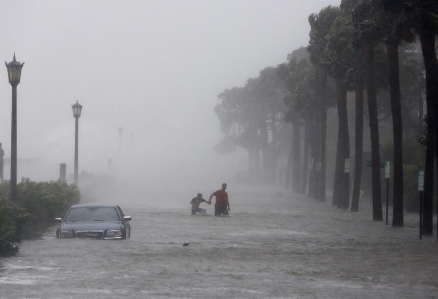 Des piétons forcés près d'une voiture inondée par Irma à Charleston, en Caroline du Sud le 11 septembre.<br /><br /> (AP)