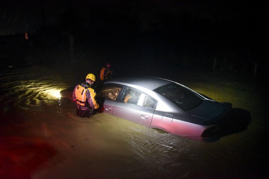 Juste de la tôle, Dieu merci. Ces secouristes constatent que cette voiture submergée est vide, à Fajarto, à Porto Rico. (AP)