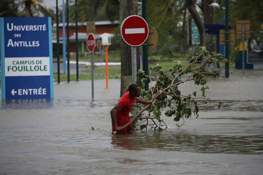 Un homme retire une branche d'une rue inondée... (REUTERS)