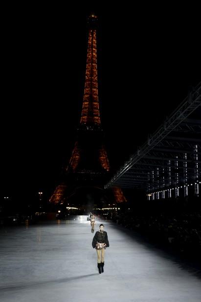 Un mannequin défile devant la tour Eiffel avec une création de Yves Saint Laurent. | 27 septembre 2017