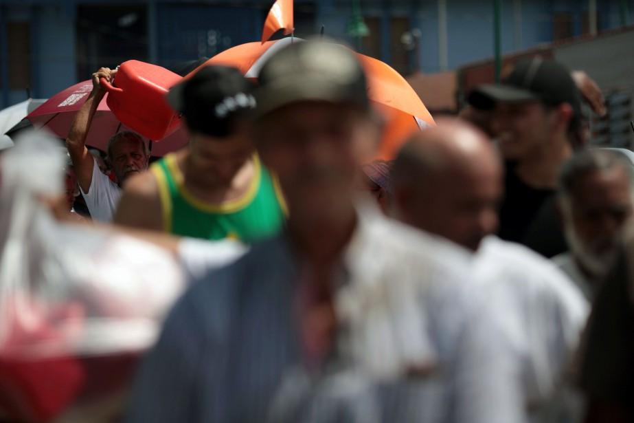 De nombreuses personnes font la queue à San... (PHOTO Alvin Baez, REUTERS)