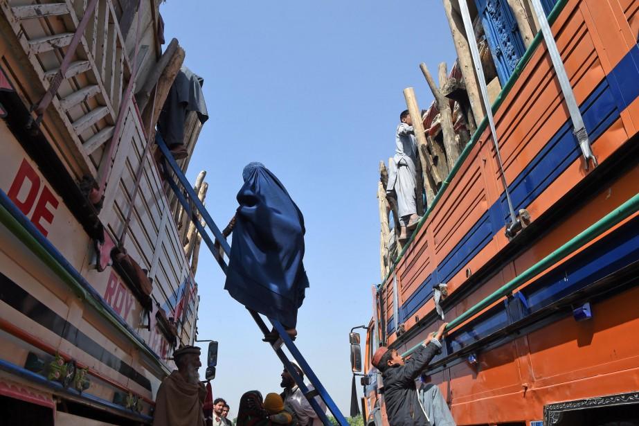 Une réfugiée afghane monte à bord d'un camion... (ARCHIVES AFP)