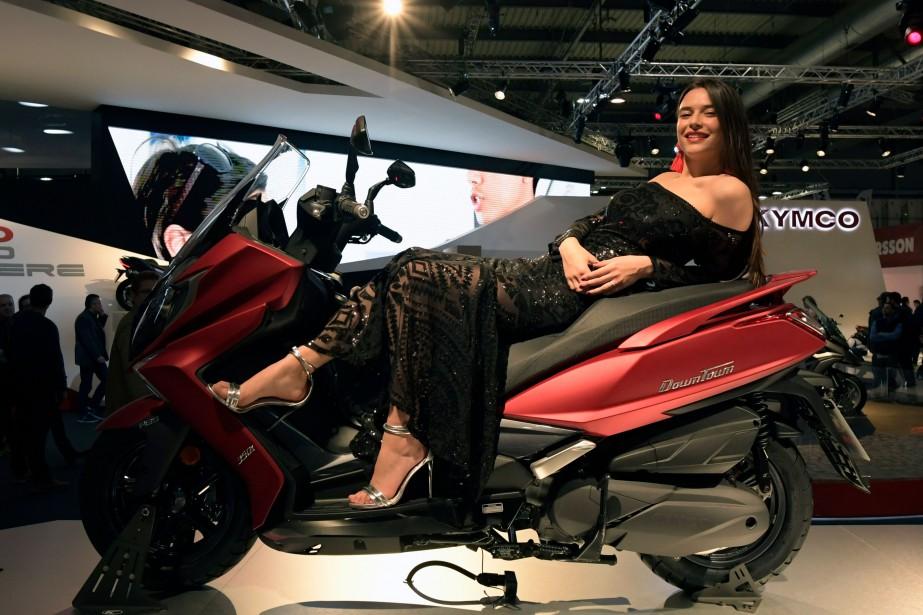 Un mannequin pose sur la Kymco Downtown 350i. À chaque présentation, le Salon de la moto EICMA de Milan donne aux amateurs et aux distributeurs une vision très complète des multiples produits qui seront offerts l ' été suivant sur le marché de la motocyclette et du scooter. | 15 novembre 2017