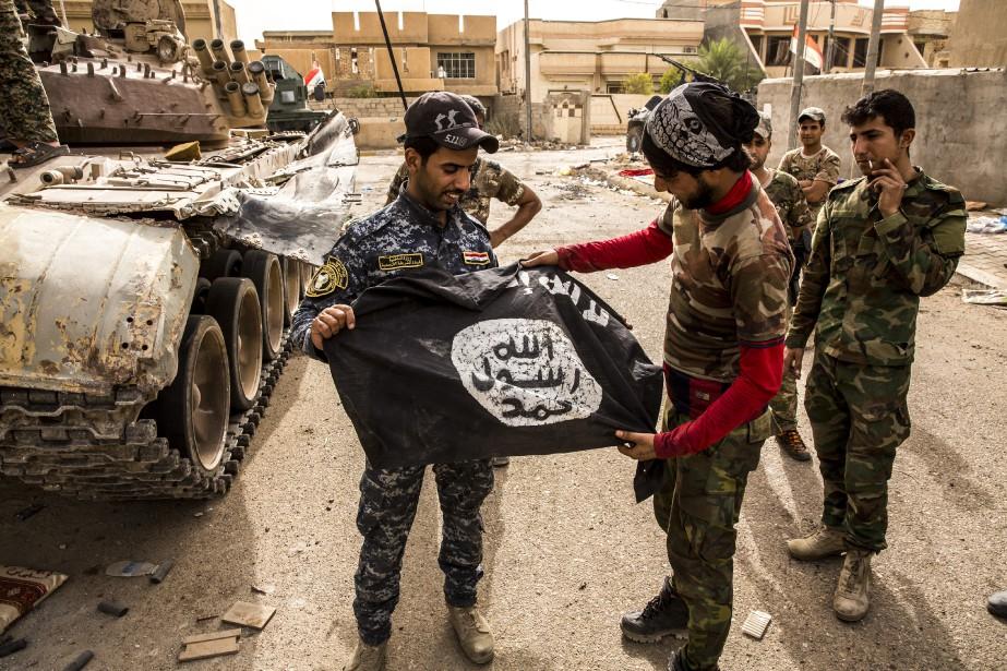 Des militaires irakiens saisissent un drapeau de l'EI... (Photo archives The New York Times)