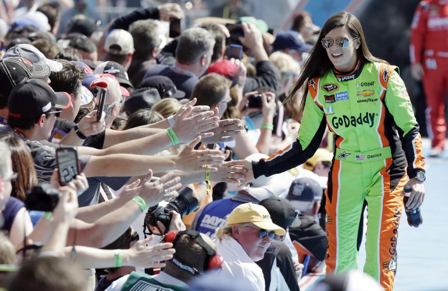 Danica Patrick salue ses fans durant la présentation des pilotes avant le départ de la course Daytona 500 de la série NASCAR Sprint Cup le 22 février 2017 au circuitDaytona International Speedway à Daytona Beach, en Floride. | 17 novembre 2017