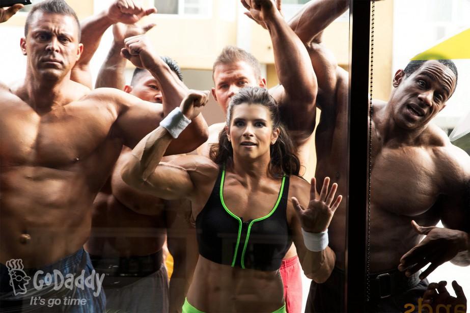 Danica Patrick figurait dans cette publicité du Super Bowl 2014 pour GoDaddy.com, avec un groupe de culturistes. La photo est retouchée, son bras droit n'est pas aussi musclé. | 17 novembre 2017