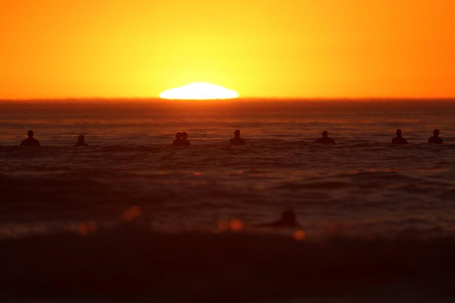 Des adeptes de surf profitent des températures clémentes... (PHOTO REUTERS)