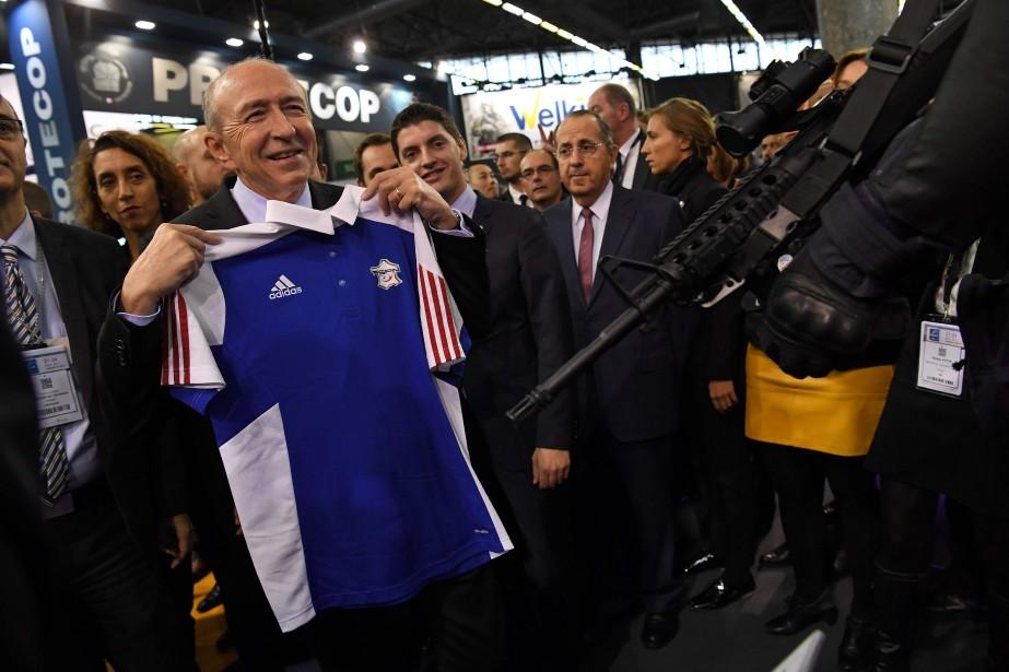 C'est un chandail Adidas et il ne s'est pas excusé de parler français chez lui. Le ministre de l'Intérieur Gérard Collomb pose avec un chandaildes équipes de France de la Fédération Sportive de la Police Nationale durant sa visite au 20e salon Minipol à Villepinte, près de Paris, le 21 novembre. (AFP)