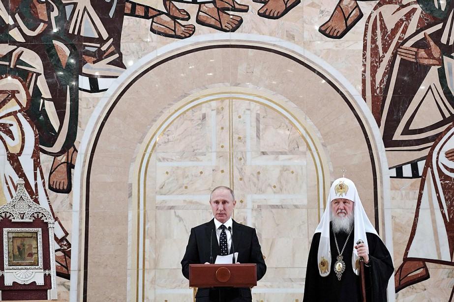 Le président russe Vladimir Poutine, accompagné du patriarche... (PHOTO ALEXEY NIKOLSKY, AFP/SPUTNIK)