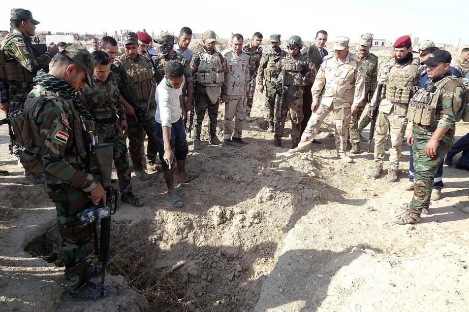 Des membres des forces irakiennes examinent un charnier... (PHOTO MARWAN IBRAHIM, ARCHIVES AGENCE FRANCE-PRESSE)