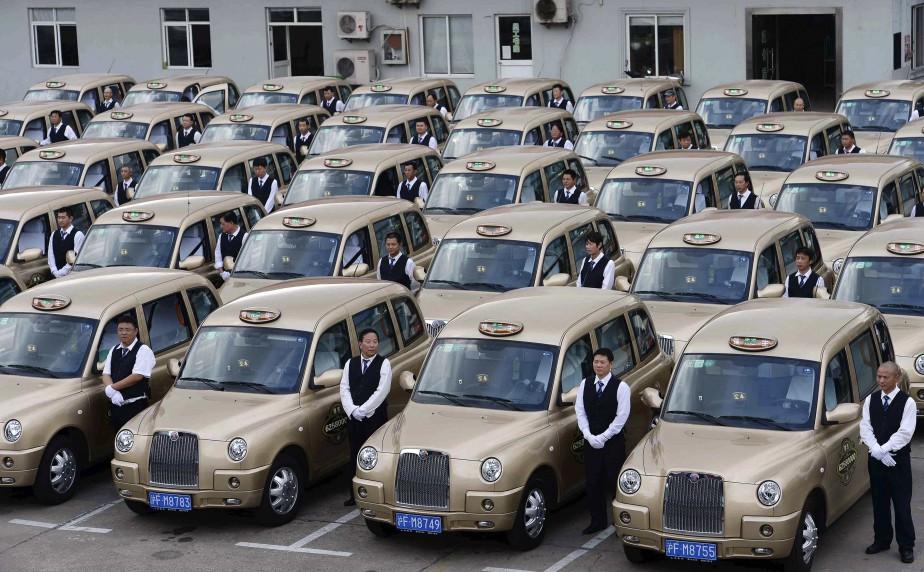 En Chine, pour le moment, on conduit des TX4 diesel, comme le montre cette photo de chauffeurs de la compagnie de taxi Qiangsheng, de Shanghai, le jour où ils ont pris possession de leur «taxis anglais Made in China», le 11 octobre 2014. | 6 décembre 2017