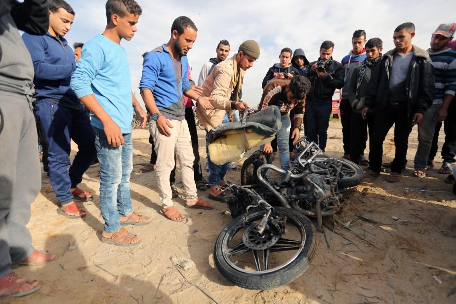 Des Palestiniens inspectent la motocyclette d'un homme qui... (PHOTO AFP)