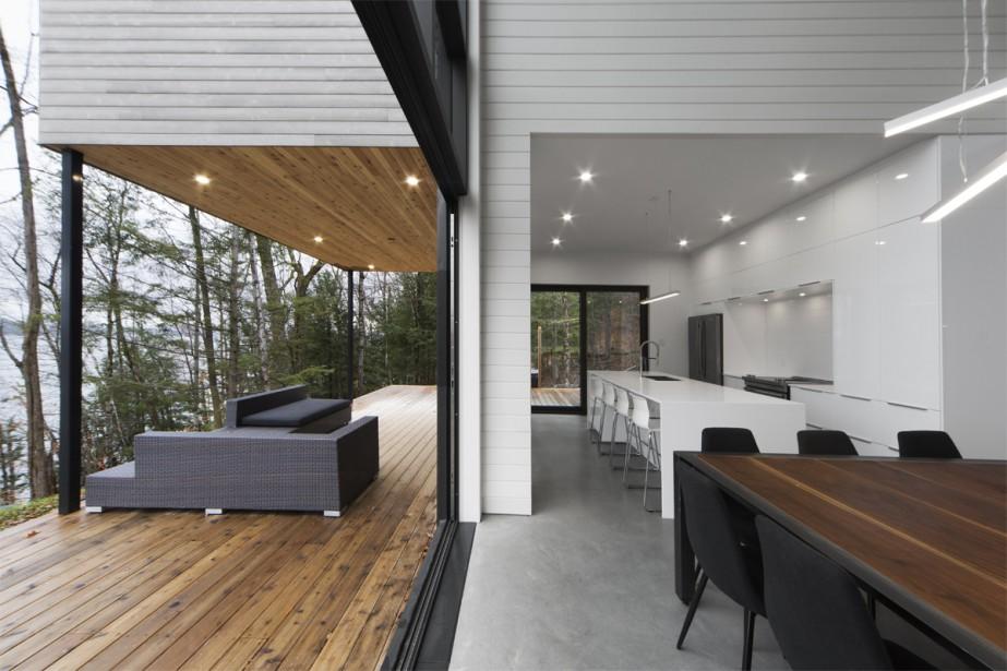 Une large porte pliante à la base du mur-rideau permet d'agrandir la salle à manger et de recevoir de très grandes tablées aux beaux jours. «On a fait un plateau pour asseoir le rez-de-jardin, car il y a un dénivelé imposant. C'était important d'avoir des espaces extérieurs connectés avec le chalet et le terrain», dit l'architecte. La symétrie entre l'intérieur et l'extérieur forme une belle perspective. | 14 décembre 2017