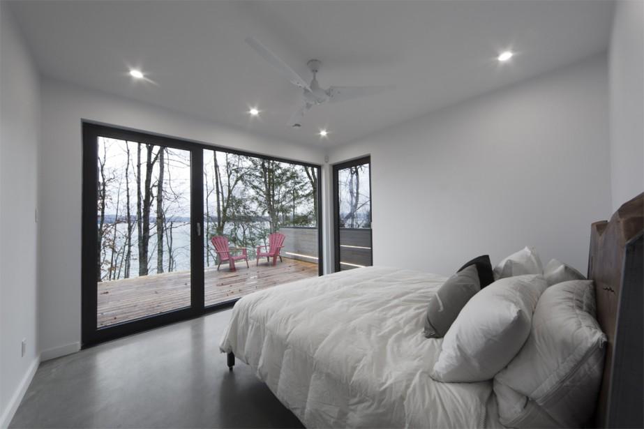 La simplicité est de mise dans toutes les chambres, y compris la principale, qui jouit d'une vaste terrasse. Rien ne laisse apparaître le garde-corps vitré, dénué de quincaillerie, à l'instar de celui de l'escalier. «C'était un facteur primordial du projet afin d'avoir le moins d'interférence possible avec le lac», précise Eric Tremblay. | 14 décembre 2017