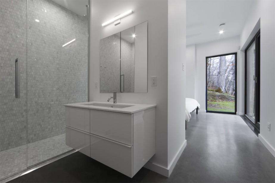 Le plancher de béton radiant dans toute la maison maximise le confort, notamment dans les salles de bains. La douche de celle-ci est revêtue de mosaïque de marbre (Ciot), dont la noblesse fait écho à celle de tous les matériaux qui habitent la demeure. Meuble-lavabo: IKEA; comptoir en quartz: Ciot; robinetterie Rubi et céramique Ramacieri Soligo. | 14 décembre 2017