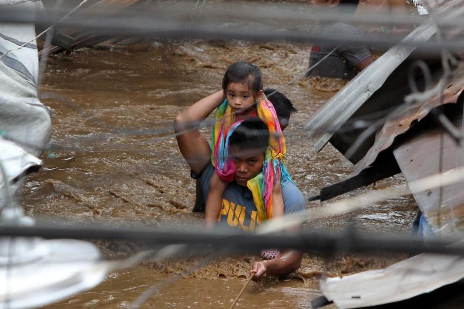 Un policier sauve une jeune fille encerclée par... (Photo Josep DEVEZA, AFP)