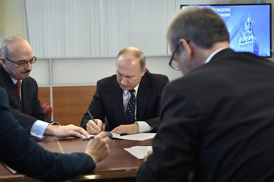 Le président Vladimir Poutine, au centre, signe un... (Alexei Nikolsky, Sputnik, Kremlin Pool Photo via AP)