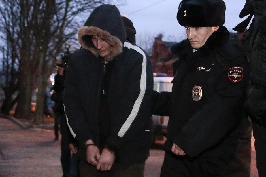 Des policiers escortent l'auteur présumé de l'attentat à... (Anton Vaganov, REUTERS)