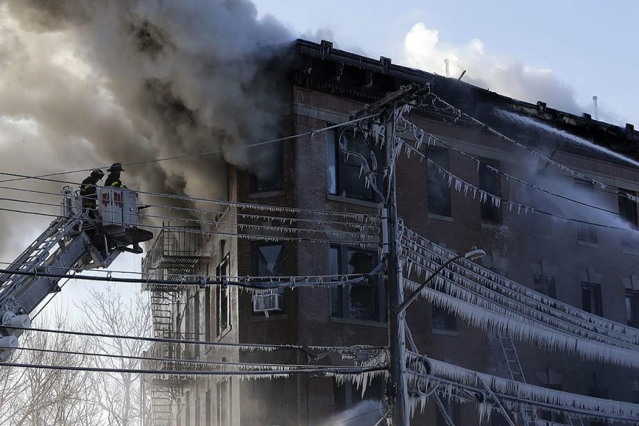 Près de l'immeuble en flammes, des glaçons pendaient... (Seth Wenig, AP)