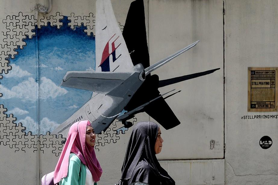 Des femmes marchent devant un graffiti en Malaysie... (MANAN VATSYAYANA, ARCHIVES AFP)
