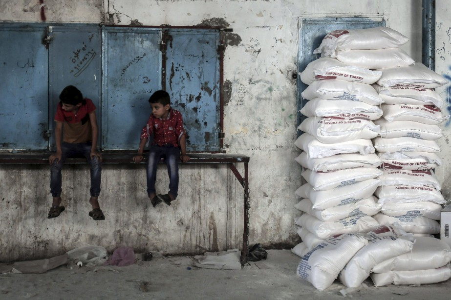Des enfants palestiniens sont assis près d'une pile... (Agence France-Presse)