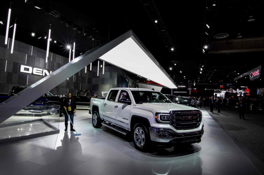 Une préposée nettoie le stand GMC avant l'ouverture du Salon de l'auto de Détroit. À sa gauche, le pick-up GMC Sierra.   | 15 janvier 2018