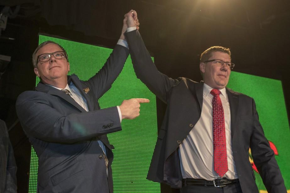 Brad Wall lève le bras de Scott Moe.... (Photo La Presse canadienne)