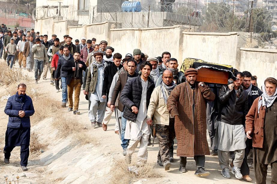 Des hommes transportent le cercueil de l'une des... (Photo Omar Sobhani, REUTERS)