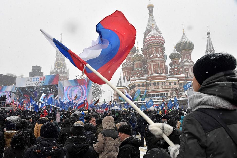 Un homme agite un drapeau russe lors d'un... (PHOTO VASILY MAXIMOV, AGENCE FRANCE-PRESSE)