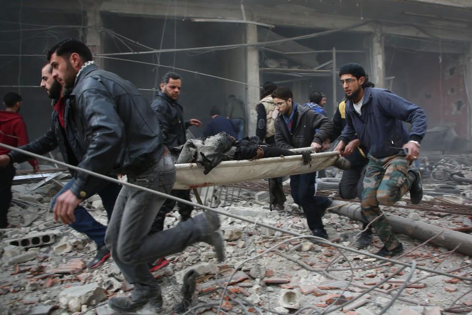 À Kafr Batna, secouristes et habitants, dans un... (Photo Amer ALMOHIBANY, Agence France-Presse)