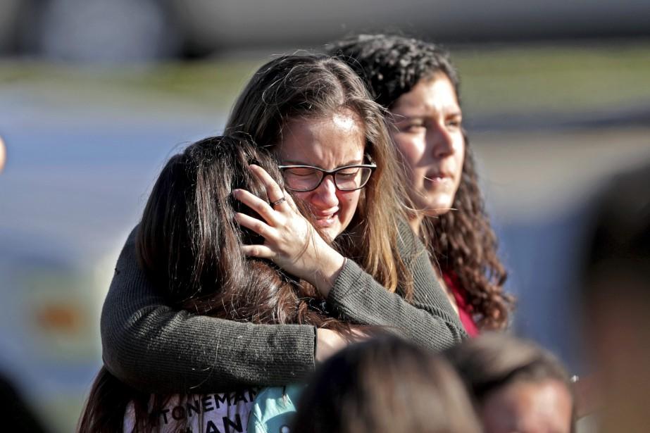 Des élèves s'enlacent après avoir évacué l'école.... (Photo John McCall, South Florida Sun-Sentinel via AP)