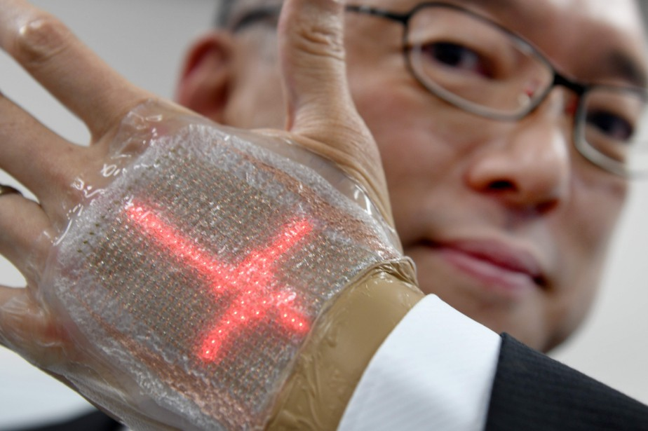 Takao Someya avec son invention sur la main.... (Photo Toru Yamanaka, Agence France-Presse)
