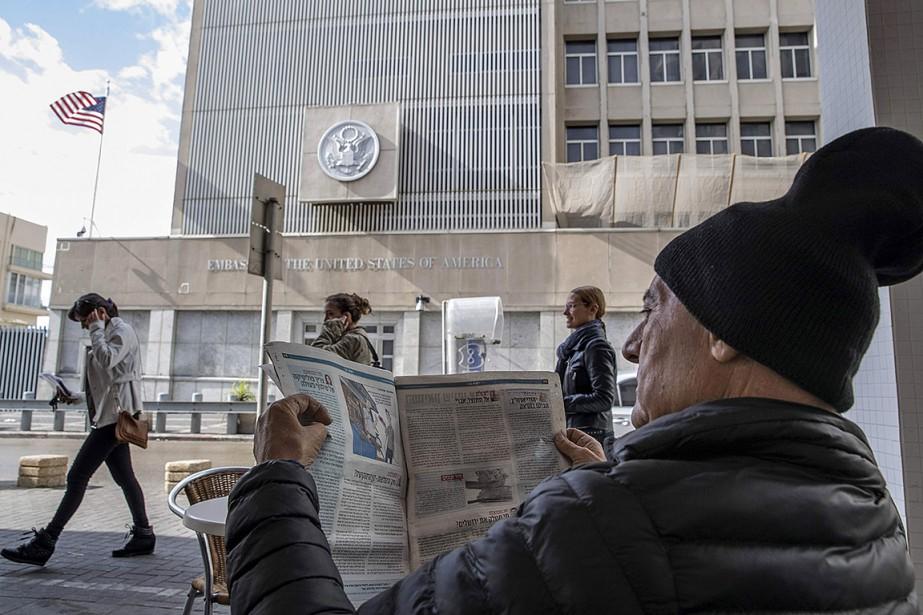 Un homme lit le journal devant l'ambassade américaine... (JACK GUEZ, archives AFP)