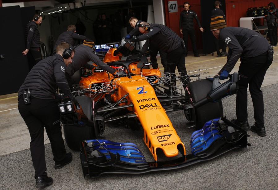 Des mécanos vêtus chaudement poussent la McLaren du Belge Stoffel Vandoorne dans le garage de l'écurie britannique. | 27 février 2018