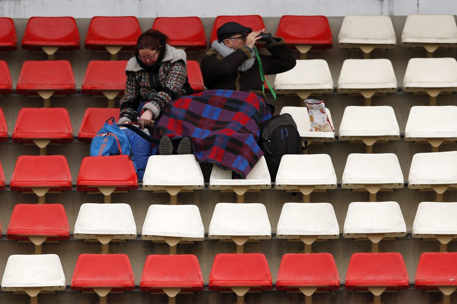A couple sits under a blanket on the...