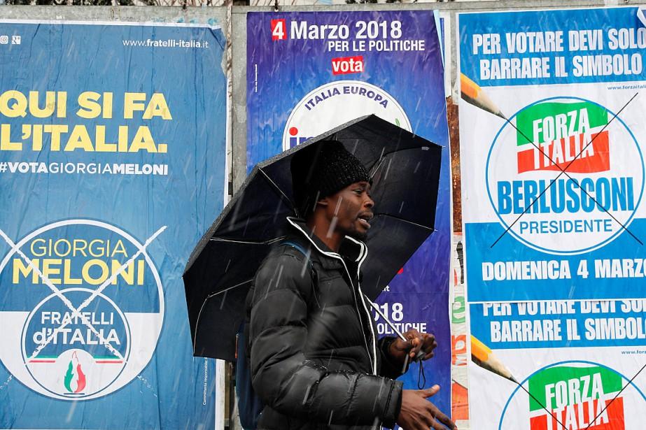 Un homme passe devant un mur où ont... (PHOTO ANTONIO CALANNI, ASSOCIATED PRESS)