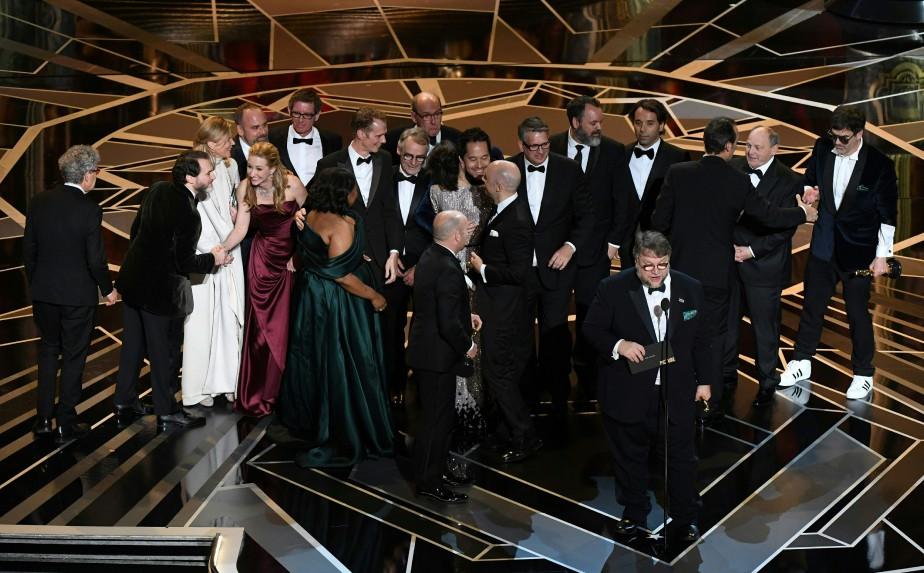 Le réalisateur Guillermo del Toro livre un discours tandis que des membres de l'équipe de son film <em>The Shape of Water</em> célèbrent leur victoire à la 90e soirée des Oscars. (AFP)