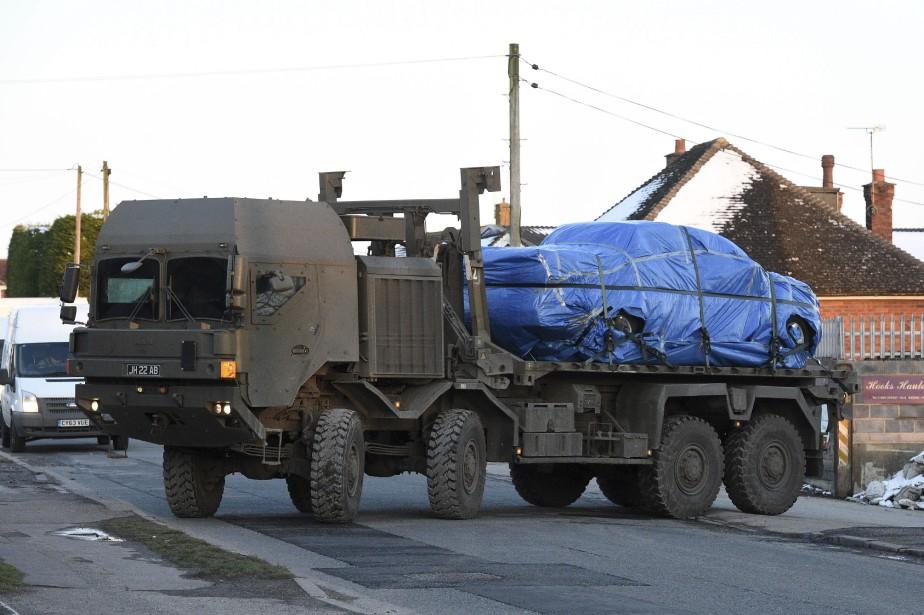 Un camion de l'armée transporte un véhicule solidement... (PHOTO Ben Birchall, AP)
