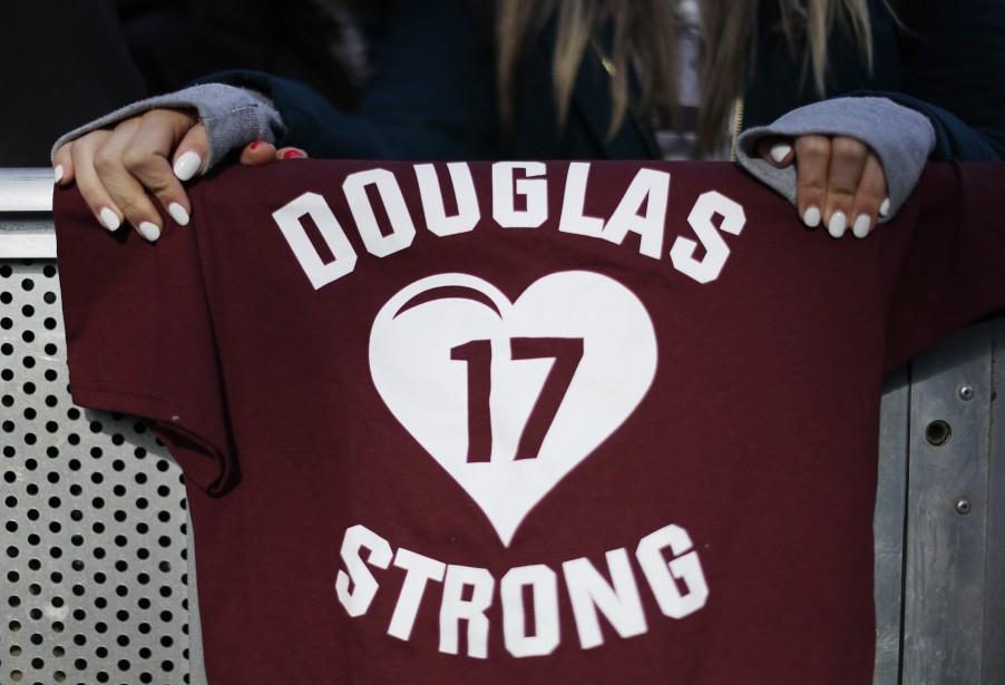 Une élève de l'école secondaire Marjory Stoneman Douglas de Parkland, en Floride, tient un chandail faisant référence aux 17victimes de la tuerie survenue le 14février lors du rassemblement à Washington.   24 mars 2018