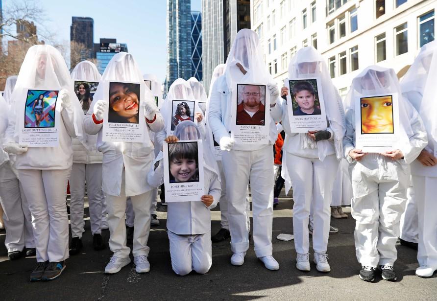 Ces gens vêtus tout en blanc tiennent des photos de victimes qui ont péri lors de fusillades dans des écoles lors du rassemblement organisé à New York.   24 mars 2018