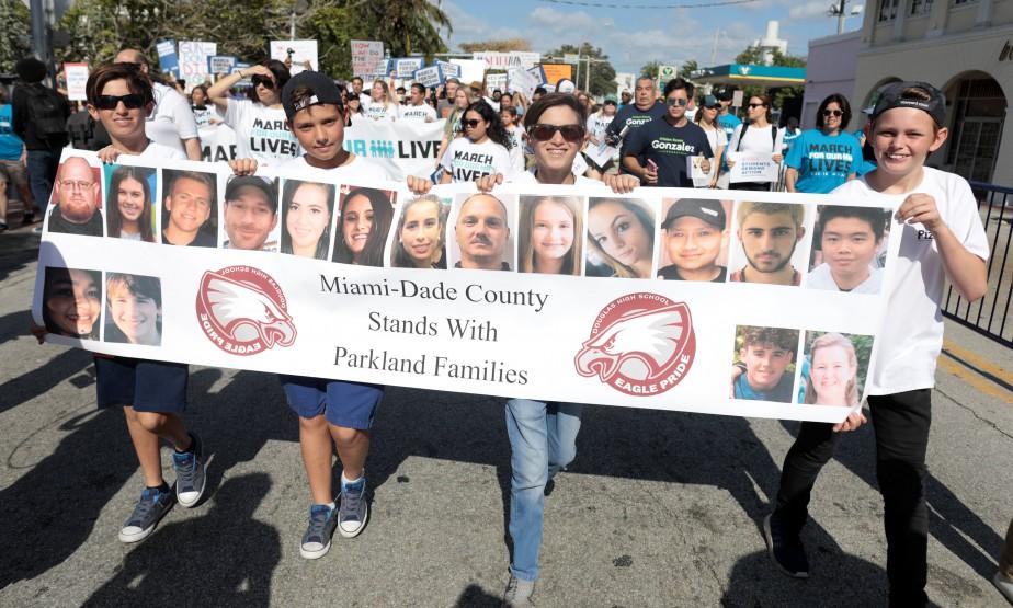 Les visages des 17victimes de la tuerie à l'école secondaire de Parkland apparaissent sur une bannière dans les rues de Miami.   24 mars 2018